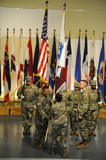 Col. David L. Sloniker accepts the colors from Maj. Gen. Barbara R. Holcomb