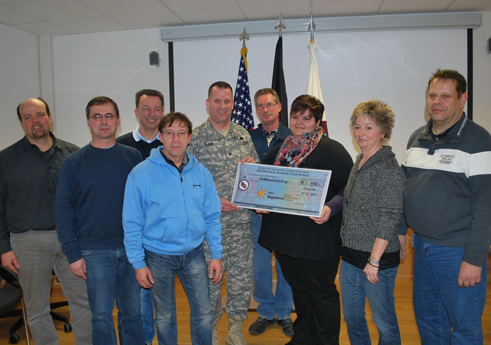 Col. Thomas C. Slade, USAMMCE commander, presents a donation check to Simone Jennewein of a local hospice.