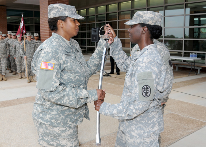 1st Sgt. Natasha A. Turrell (left) accepts the noncommissioned officer's sword from Capt. LaShawnna Ray (right)