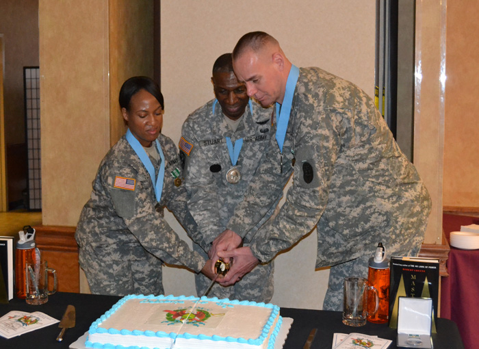 Staff Sgt. LaDonna Tolbert (left) and Staff. Sgt. Patrick Omara (right) cut the celebratory cake with Command Sgt. Major Kevin B. Stuart, USAMRMC command sergeant major