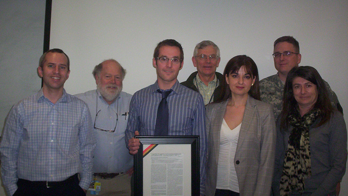 Dr. Jason Koontz successfully defends his thesis and is presented with a framed copy of his first authored work