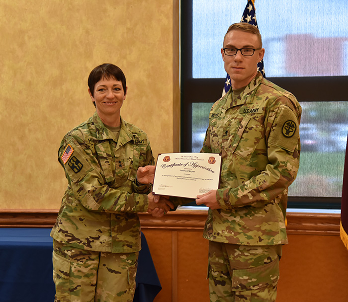 Maj. Gen. Barbara R. Holcomb presents Spec. Joshua Meyer with this award