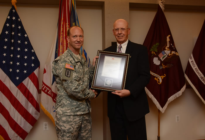 Col. David R. Gibson accepts the command's Wolf Pack Award from Gregg Stevens