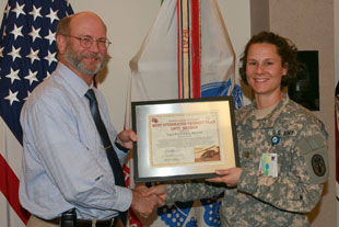 Dr. Kenneth Bertram (left) awards Maj. Kara Schmid