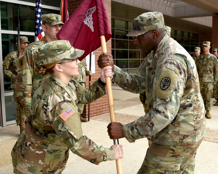 First Sgt. Brittney Graham takes guidon from Capt. Cleveland Bryant Jr.